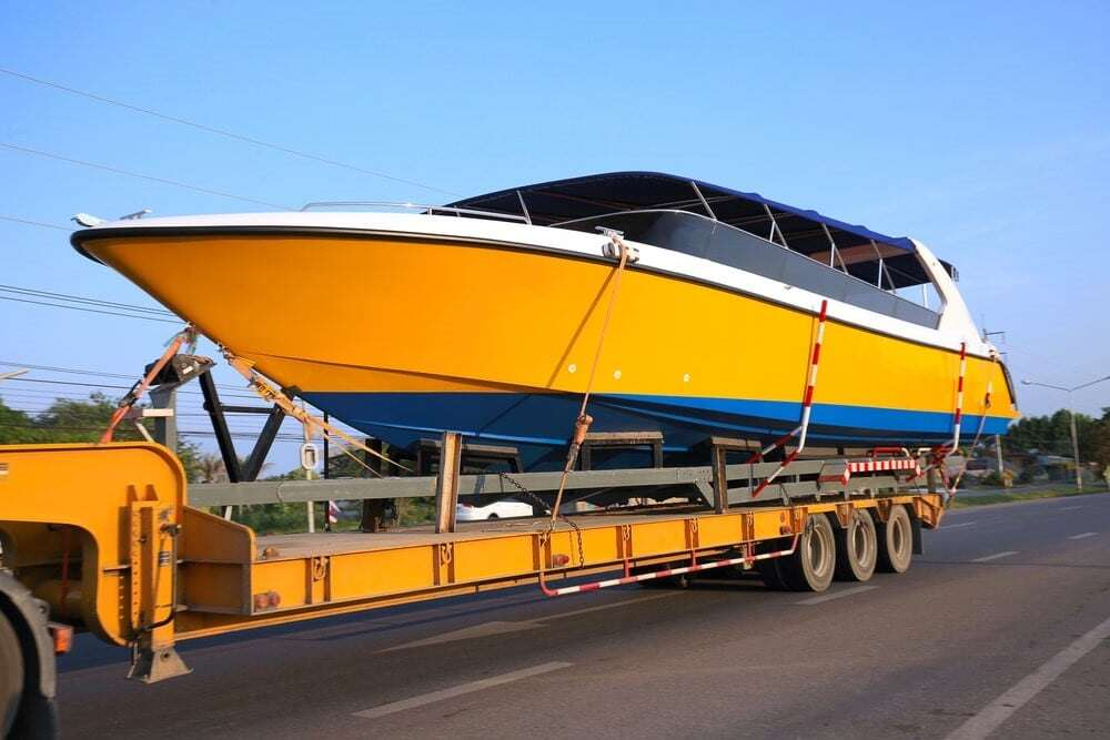 Boat being shipped on a truck bed.
