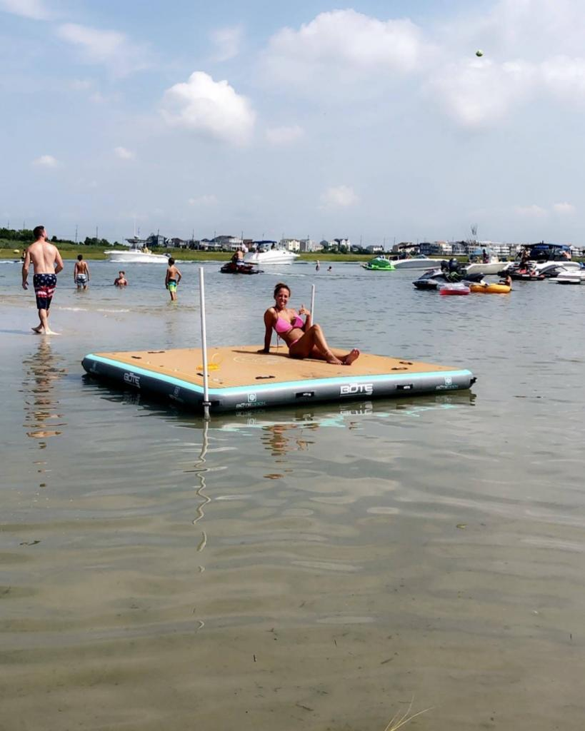 The Bote Inflatable Dock 10x10 with a girl on it.