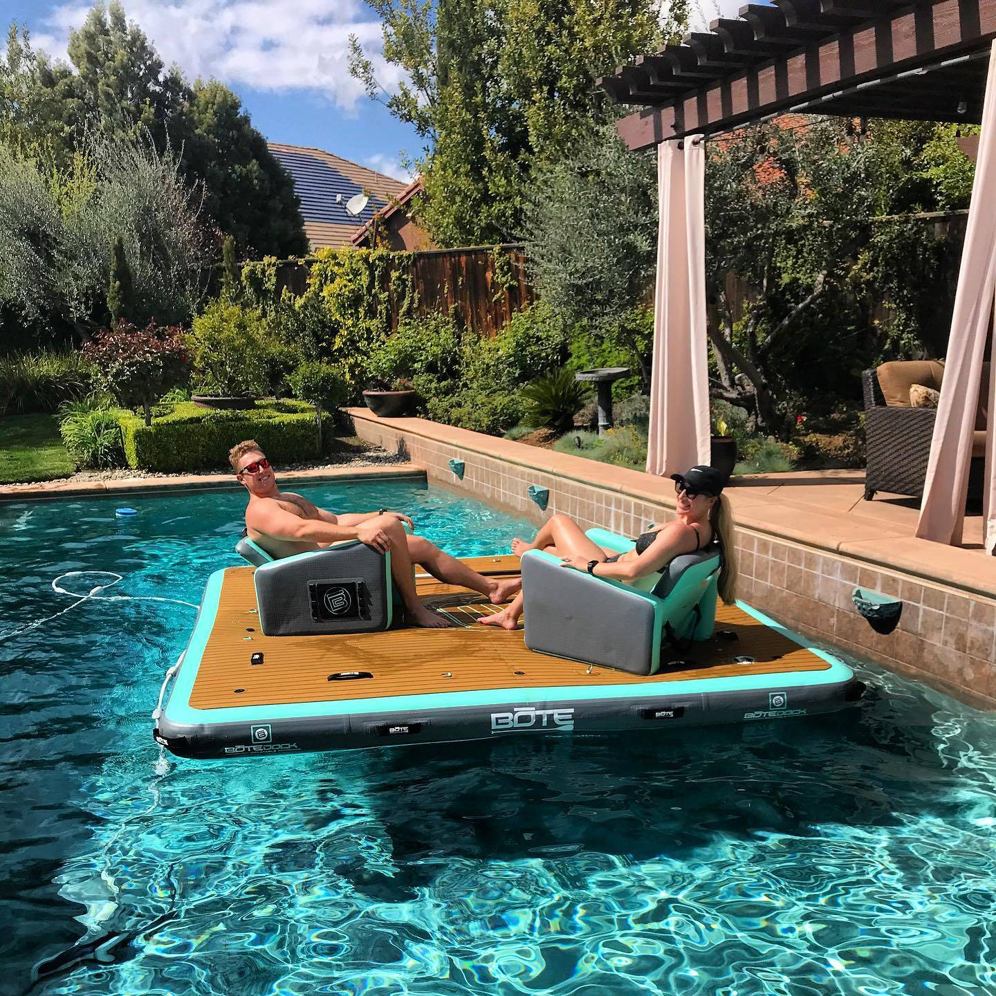 Two people on a seat in a pool gives you an idea of the size of the 7x7 Bote Inflatable Dock.