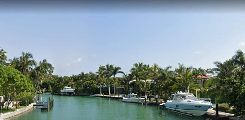 Canal homes with boats on boat lifts in Miami Beach, FL.