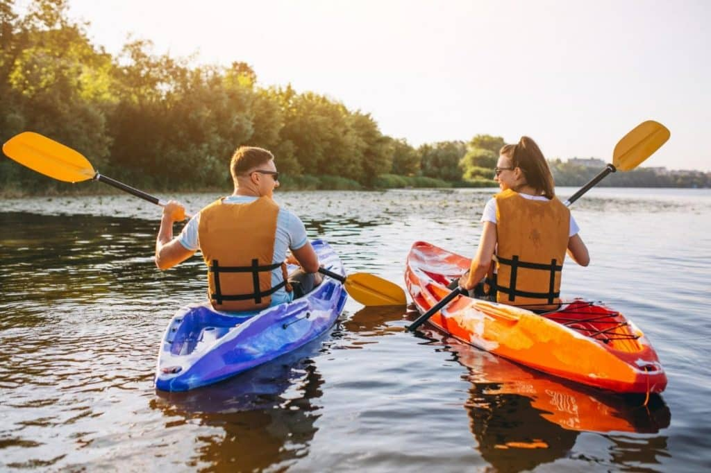 A couple seen from behind on kayaks.
