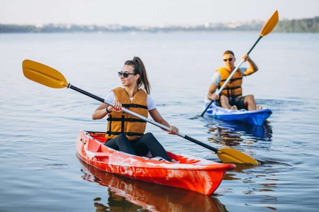 Girl kayaking with another person on another kayak.
