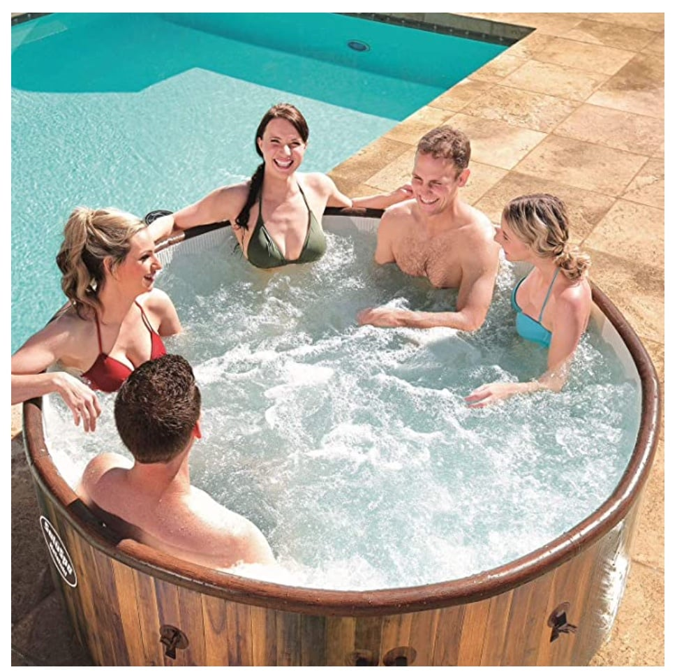 Inflatable hot tub with friends by a pool.