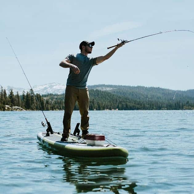 Guy casting and fishing on an inflatable paddle board.